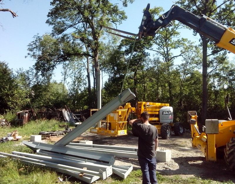 Un poteau est déjà en place, mais au niveau de l'arbre derrière lui, et là, ils montent le 2ème poteau