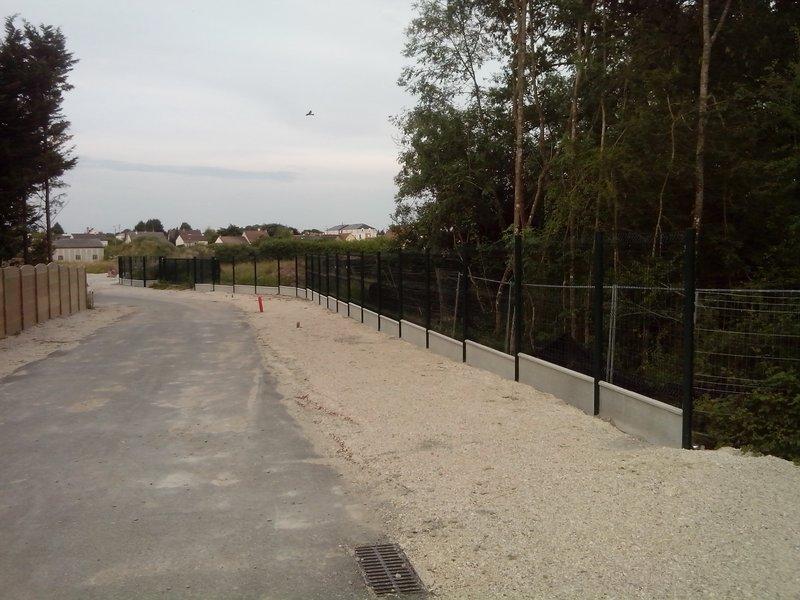 La clôture côté ouest, avec derrière un gros tas de terre à évacuer